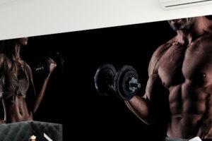 atletyczna para z hantlami na czarnym tle - fototapeta do siłowni, klubu fitness