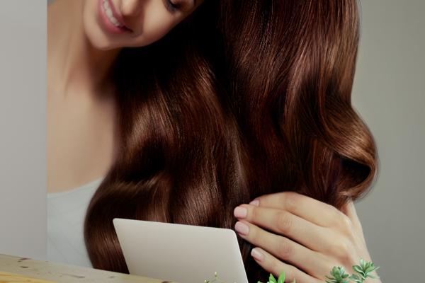 kobieta prezentuje długie falowane kasztanowe włosy - fototapeta do salonu fryzjerskiego