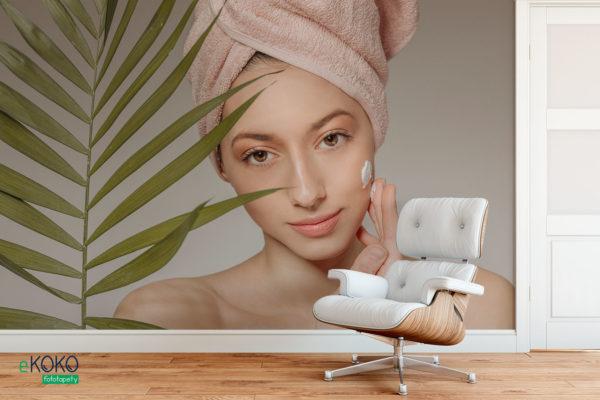 kobieta z ręcznikiem na głowie nakłada krem - fototapeta do salonu kosmetycznego