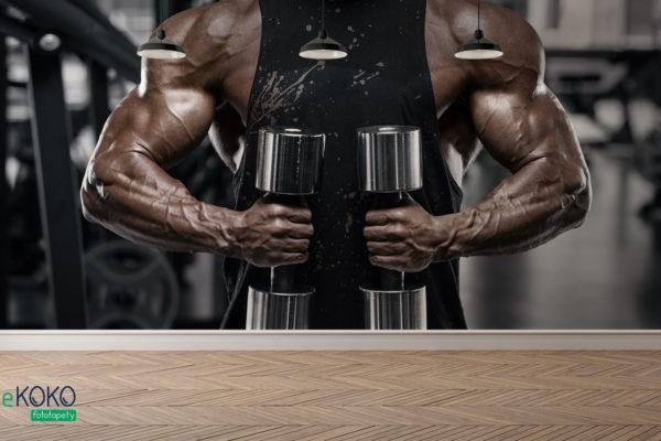 muskularny facet w czarnej koszulce ze srebrnymi hantlami - fototapeta do siłowni