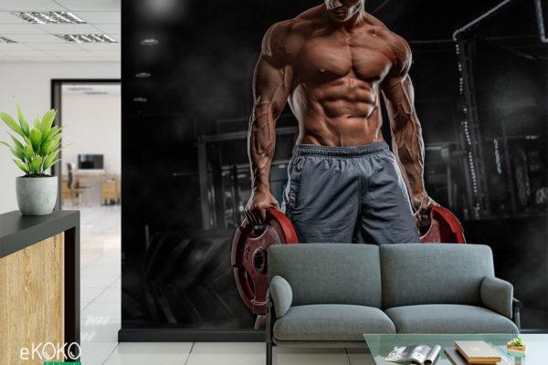 muskularny facet w szarych spodenkach z ciężarami na siłowni - fototapeta do siłowni, klubu fitness