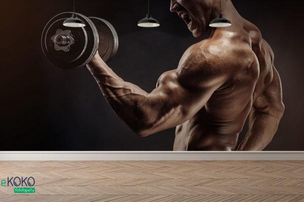 muskularny facet z hantlami ćwiczy mięśnie rąk - fototapeta do siłowni