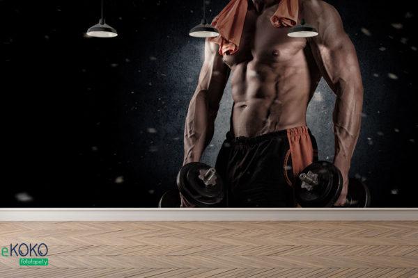muskularny facet ze zdjętą koszulką pozuje z hantlami - fototapeta do siłowni, klubu fitness