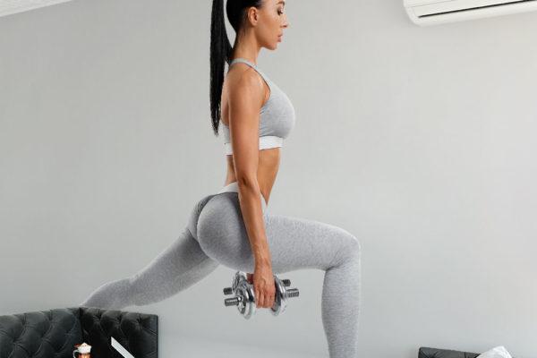 wysportowana brunetka w szarym stroju z hantlami ćwiczy mięśnie nóg - fototapeta do siłowni, klubu fitness