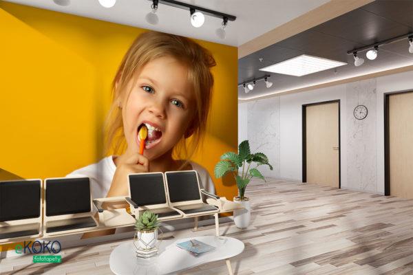 dziewczynka w białej koszulce czyści zęby na żółtym tle - fototapeta do gabinetu stomatologicznego