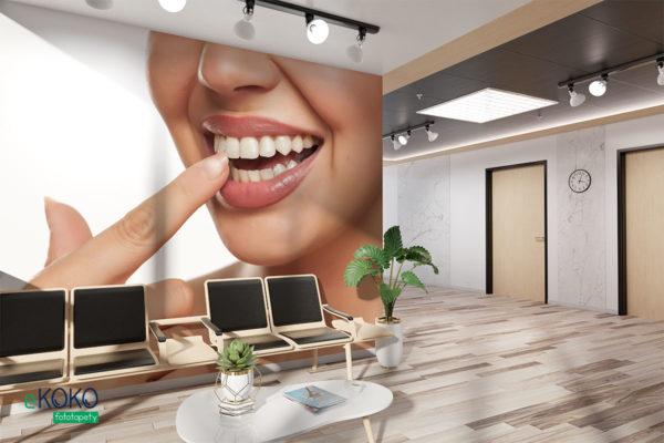 kobieta wskazuje palcem swoje białe zęby na jasnym tle - fototapeta do gabinetu stomatologicznego