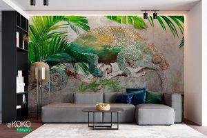 kameleon na gałęzi wśród tropikalnych roślin na betonowym tle – fototapeta